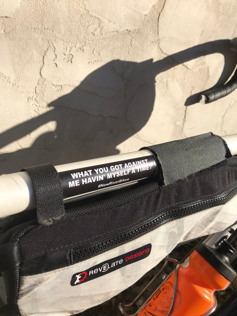 Top tube of a Surly Midnight Special bike with a gear bag and sticker leaning on tan stucco wall