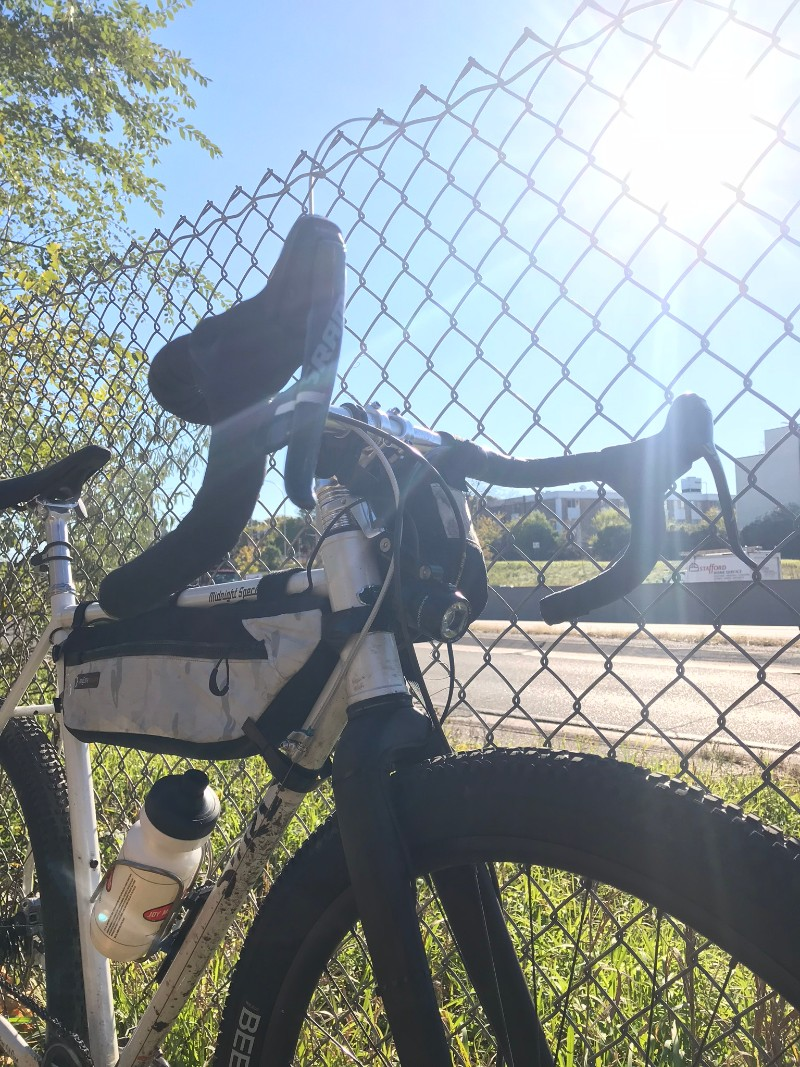 Surly Midnight Special bike leaning on a chain link fence on a sunny day next to a roadway