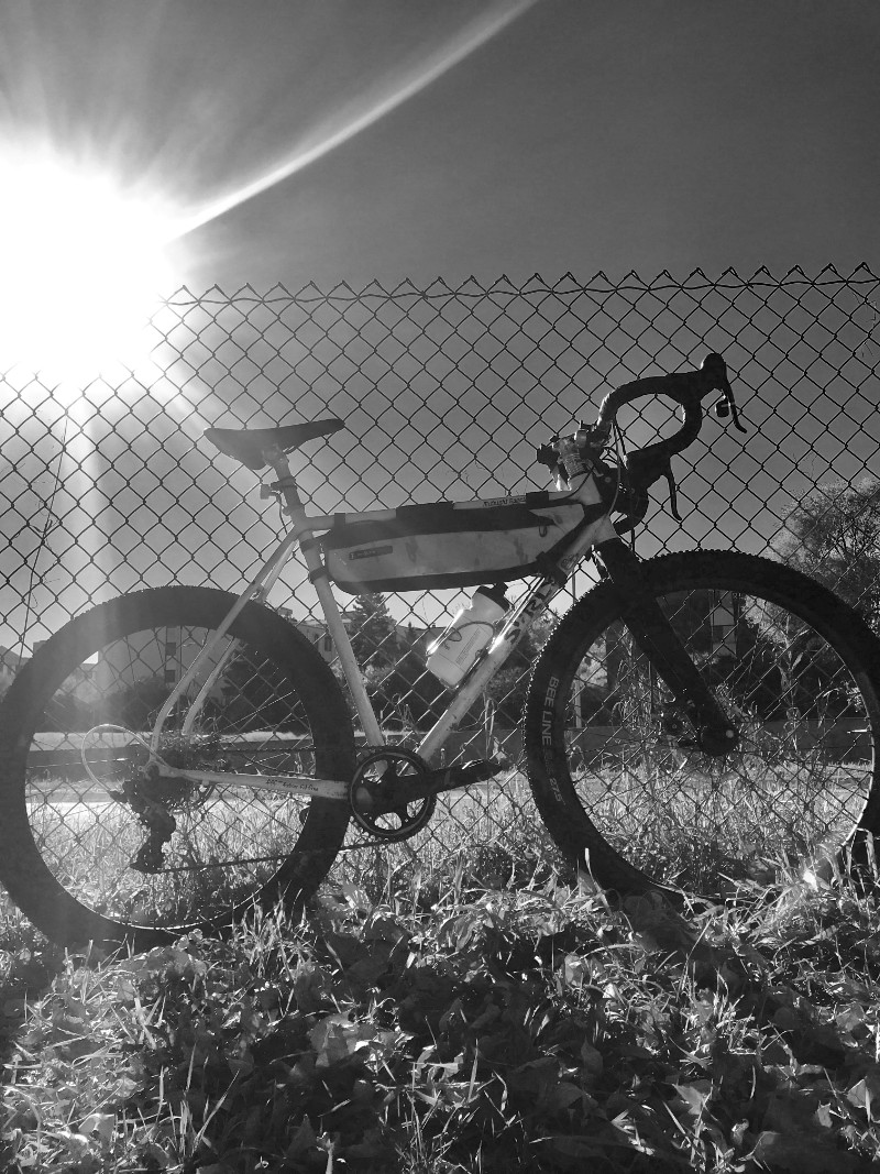 Right side view in black and white photography of a Surly Midnight Special leaning on a chain link fence in the grass