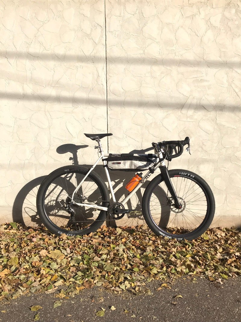 Right side view of a white Surly Midnight Special bike leaning on a tan stucco wall with leaves on the ground