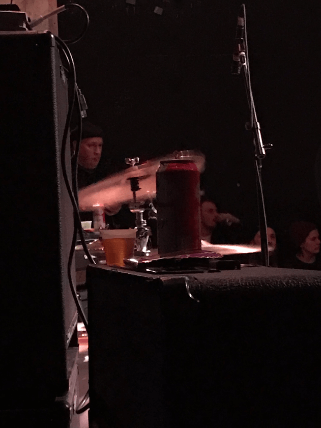 Two speakers with one having a couple of beers on top with a drummer and drum set in the background