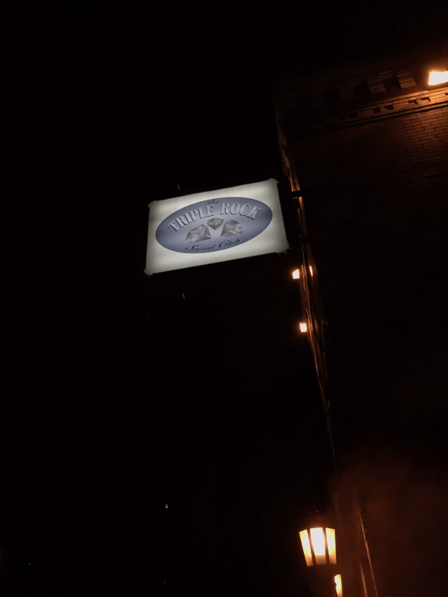 Upward side view of a Triple Rock social club sign on the outside of a building at night