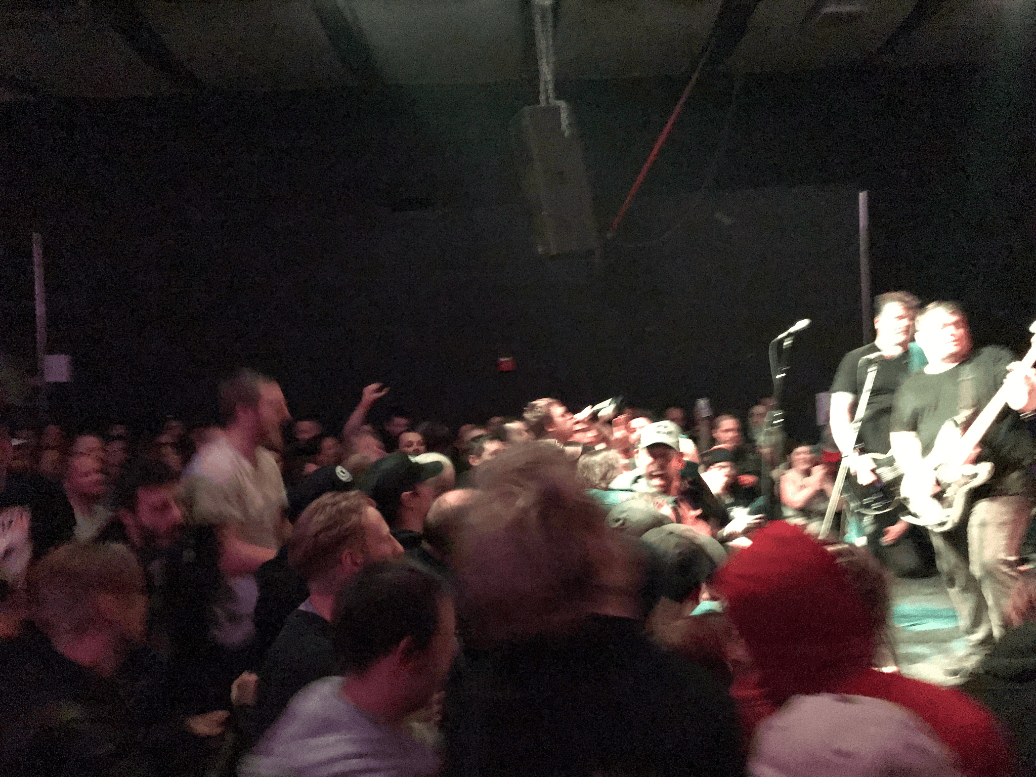 A blurry right side view of people looking up to a lighted stage in a dark room