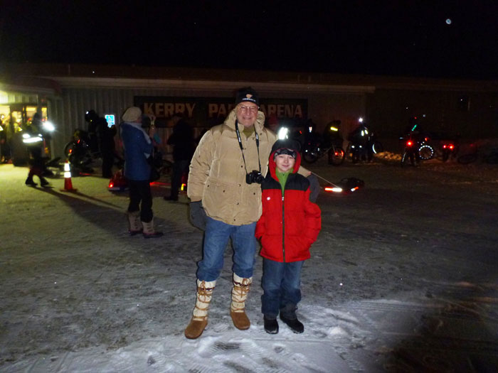 Front view of an adult and a child, standing side by side in front of a building, on a snow covered parking lot at night