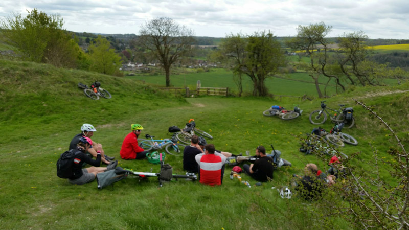 A group of cyclist sitting on a grassy hills with their bikes, with trees and hills in the background