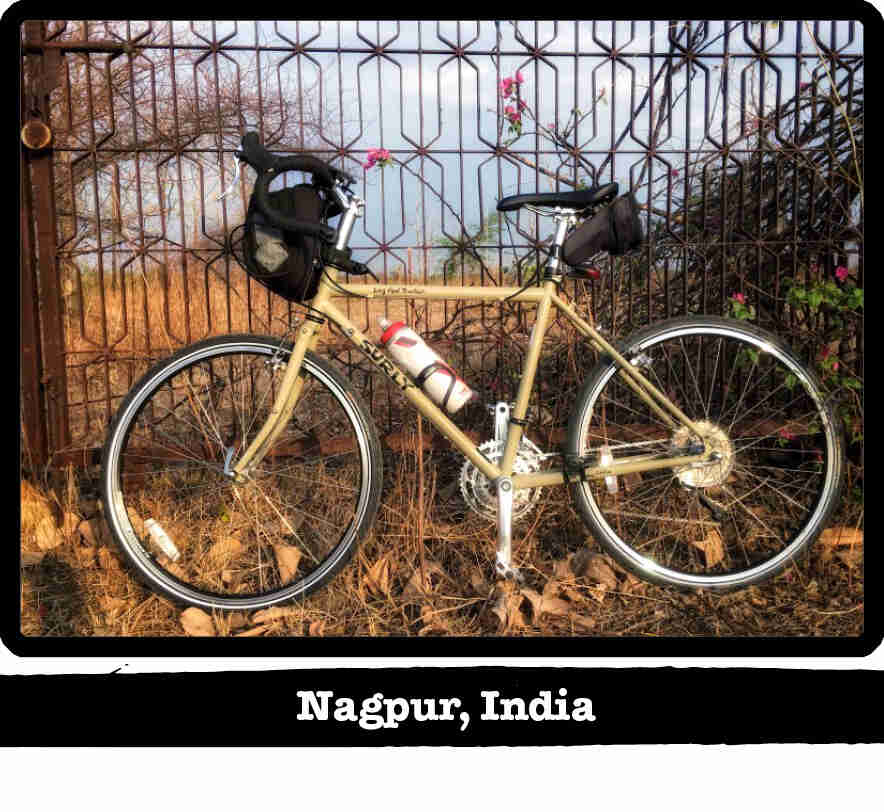 Left profile of a Surly Long Haul Trucker bike, tan, leaning of a steel rod fence - Nagpur, India tag below image