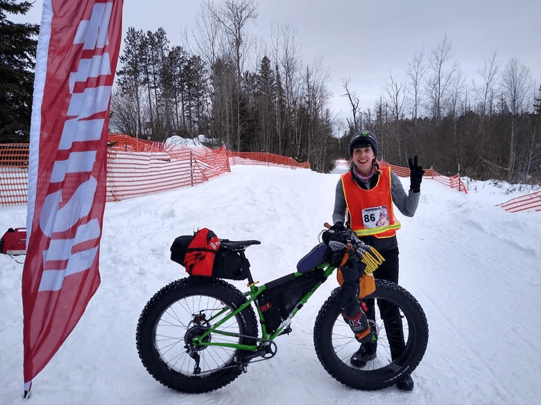Cyclist smiles giving a peace sign while standing with  their fat bike, green, at a finish line of a snowy bike trail