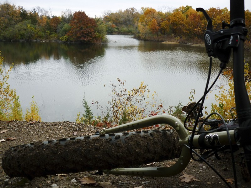 Front end view of a green Surly fat bike, laying on a dirt bank with a pond below, and changing trees in the background