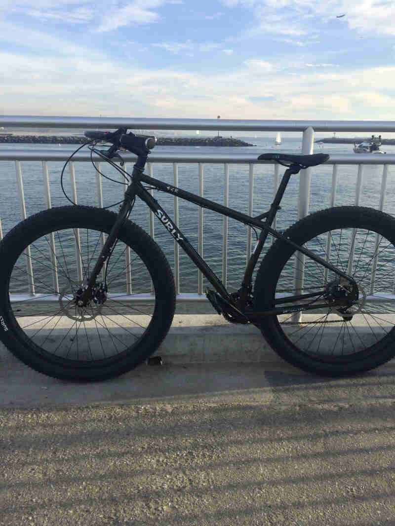 Left side view of a black Surly ECR bike, parked along a steel handrail with a bay behind it