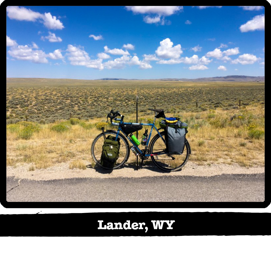 Left side view of a Surly bike on the side of the road with a wire fence and plains behind-Lander, WY banner below image