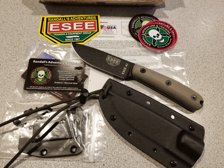 Black blade ESEE knife lying next to black sheath with Randall's Adventures & Training shirt patches and business card