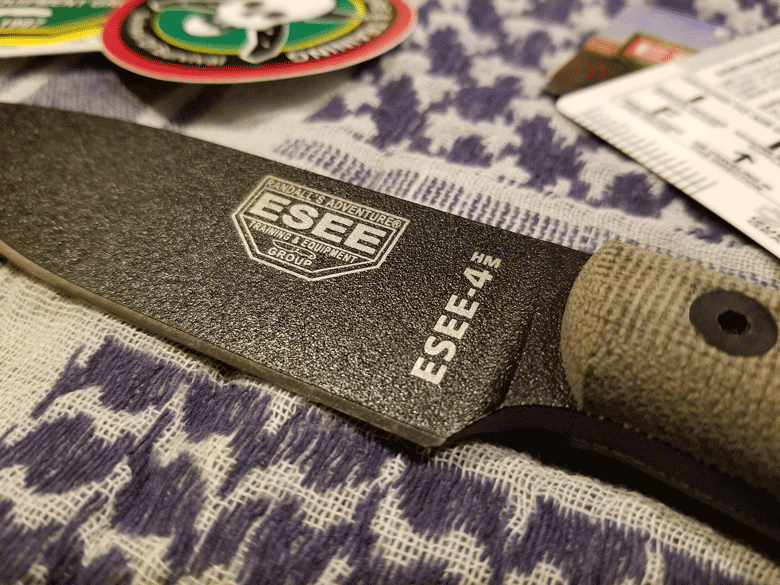 ESEE 4HM knife with black powder coated and showing small portion of a tan handle lying on woven blue and white blanket