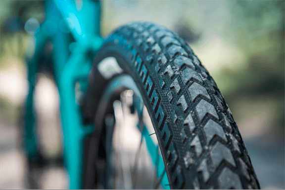Surly ExtraTerrestrial tire - Rear tire tread detail - Mounted on rear rim on a turquoise bike - Rear view