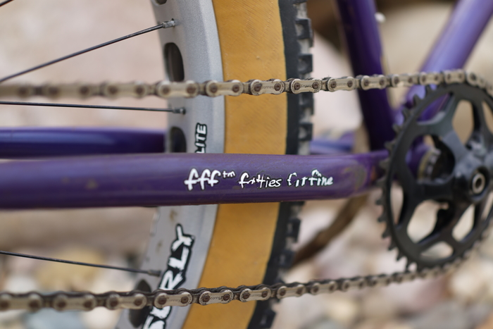 Right side, angled close up of zoom in of a fat bike tire, chain and crankset on a purple Surly Pugsley fat bike