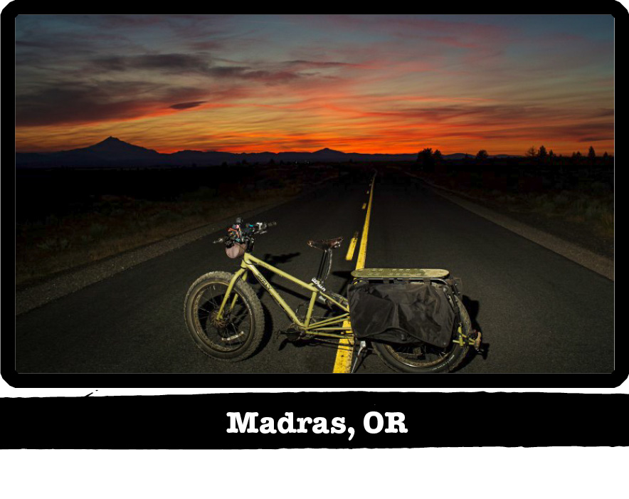 Left side view of Surly Big Fat Dummy bike, green, standing across a highway at sunrise - Madras, OR tag below image