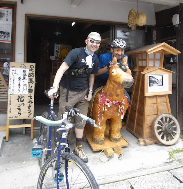 A cyclist standing with a Surly Travelers Check bike, blue and a person standing behind a wooden horse at a store front