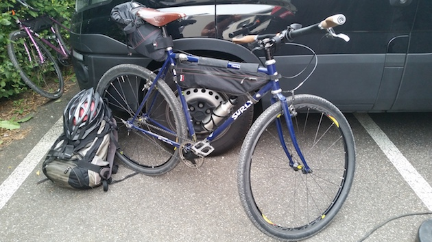 Right side view of a Surly Travelers Check bike, blue with a helmet and backpack laying near on a parking lot