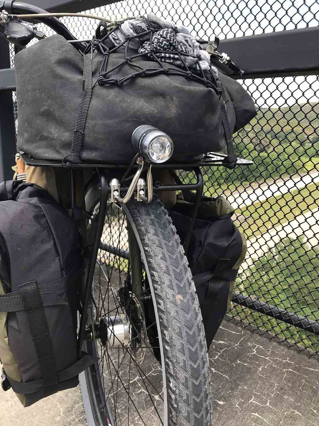 Front view close up of bike on paved trail bridge with black gear pack attached to rack,black saddle bags and headlight