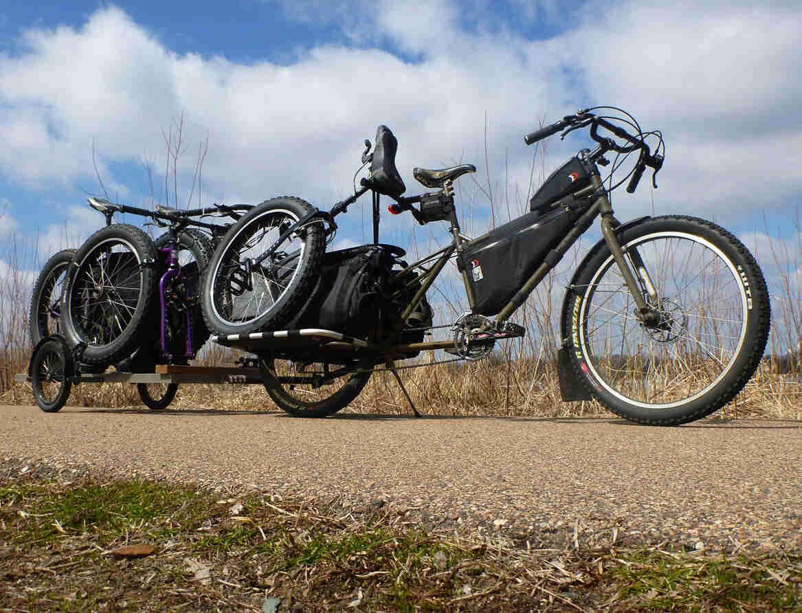 Right side, ground level view of a Surly Big Dummy bike, with a unicycle on back, and loaded trailer hitched behind