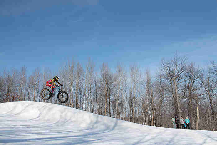 Right side view of a cyclist going airborne on a fat bike at a ski hill, with trees and blue sky in the background