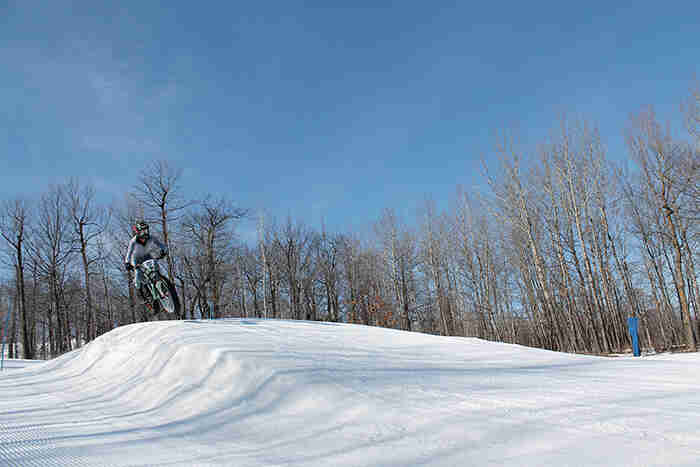 Front view of a cyclist on a fat bike, going airborne off of a berm at a ski hill, with trees in the background
