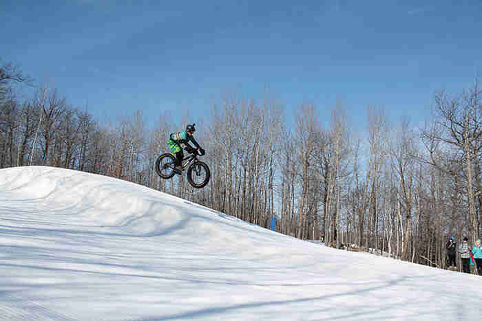 Right side profile view of a cyclist, going airborne on a fat bike at a ski hill, with trees in the background