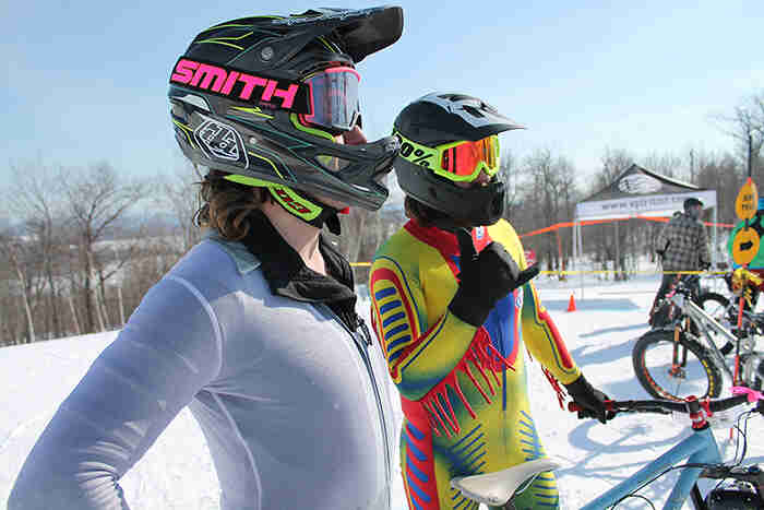 Right profile view of two cyclists wearing helmets and bike race suit, at the bottom of a ski hill
