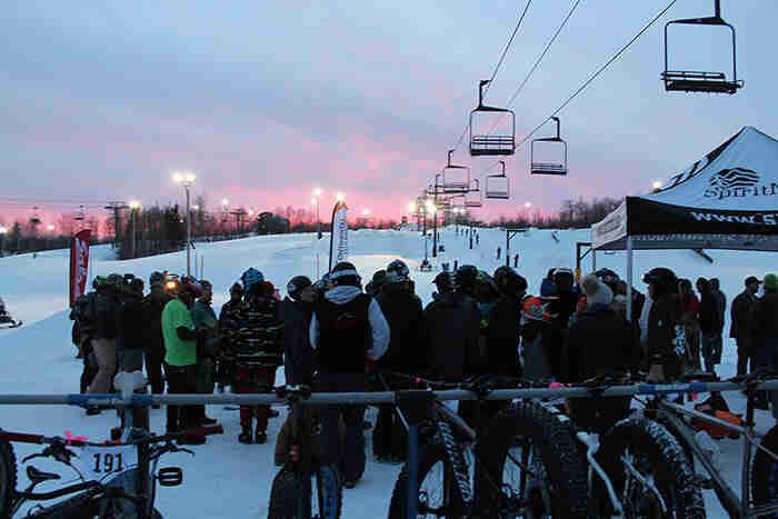 Rear view of spectators looking up a ski hill, with ski lift cars above, at dusk