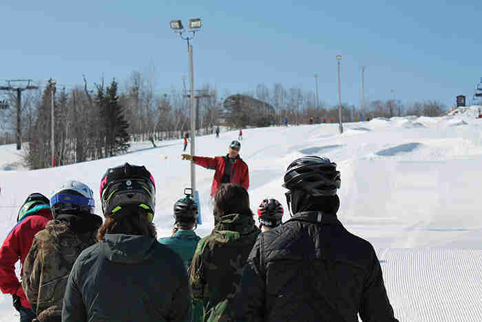 Rear view of people facing a person speaking at a ski hill