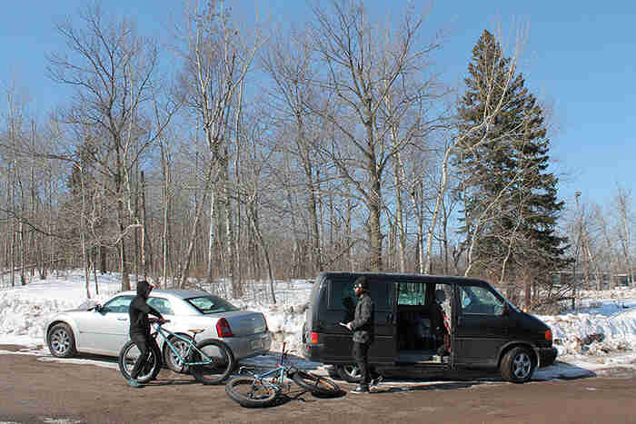 Two cyclists standing on a road next to their bikes beside a van and car, with snowy ground and trees in the background