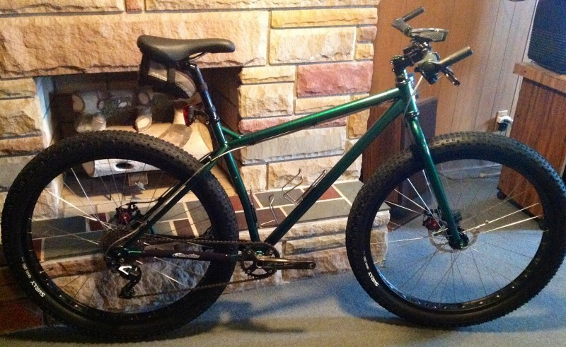 Right side view of a green Surly Krampus bike, leaning on the base of an interior, stone fireplace