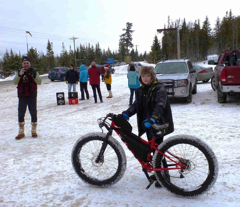 Left side view of a red Surly fat bike, with a kid standing on the right side, on a snow covered parking lot