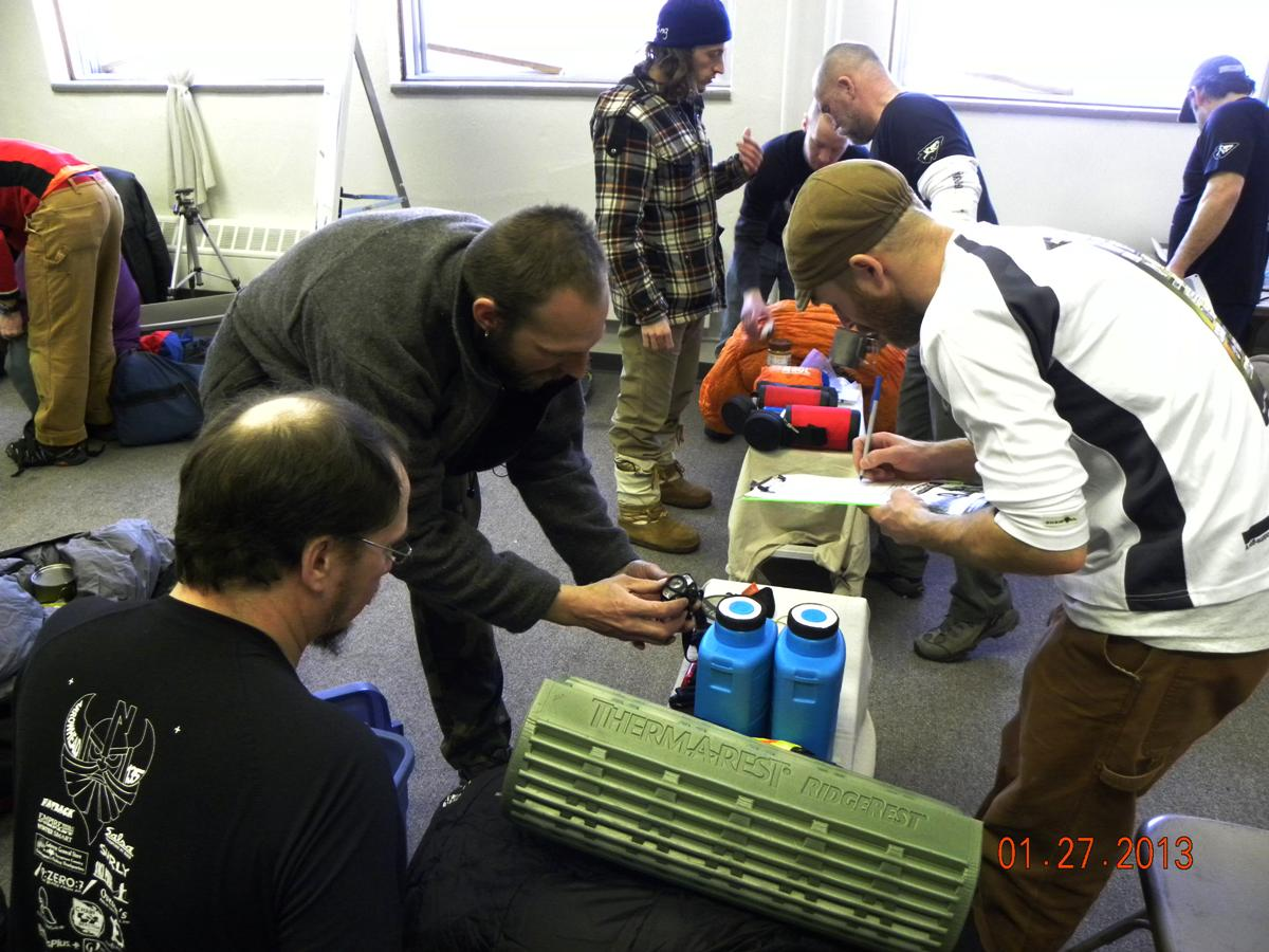 Side view of a group of people sorting through camping gear inside of a room