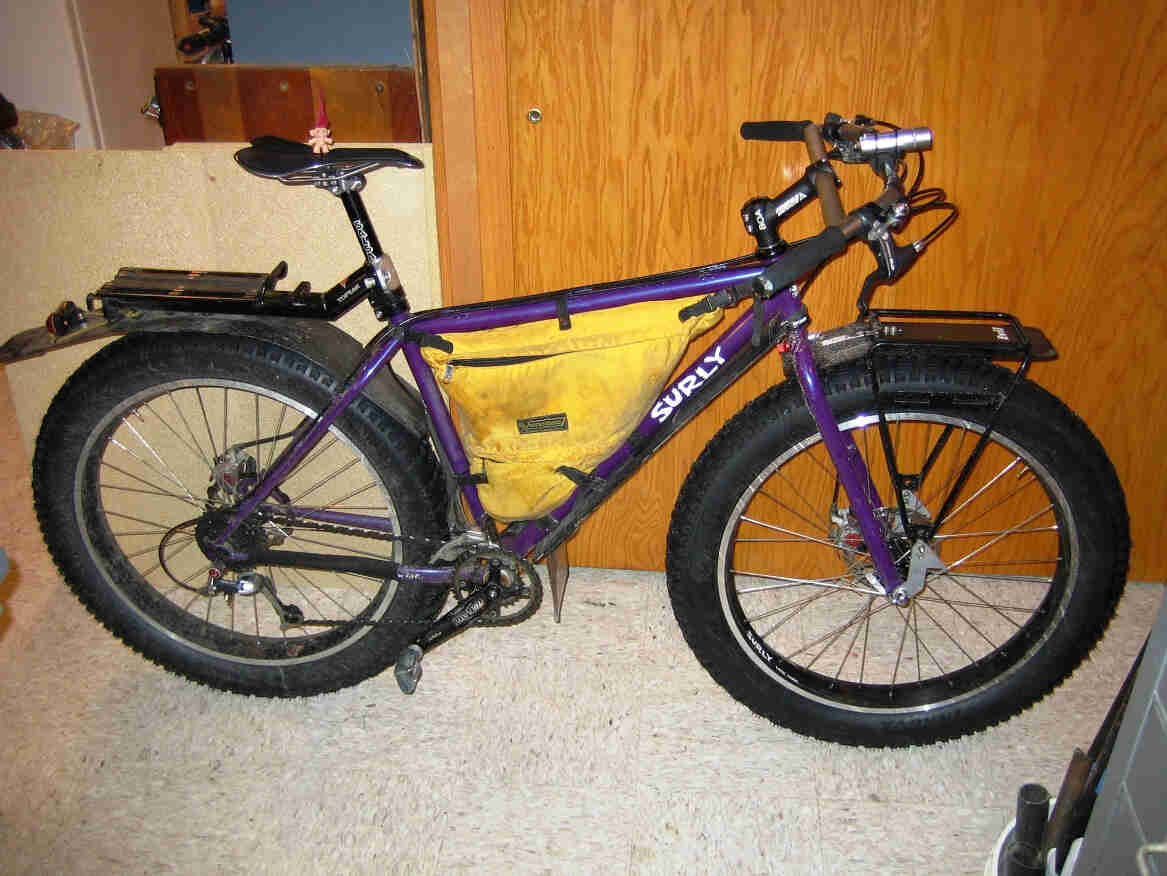 Right side view of a purple Surly Pugsley fat bike with frame pack, leaning against a wood wall in a room