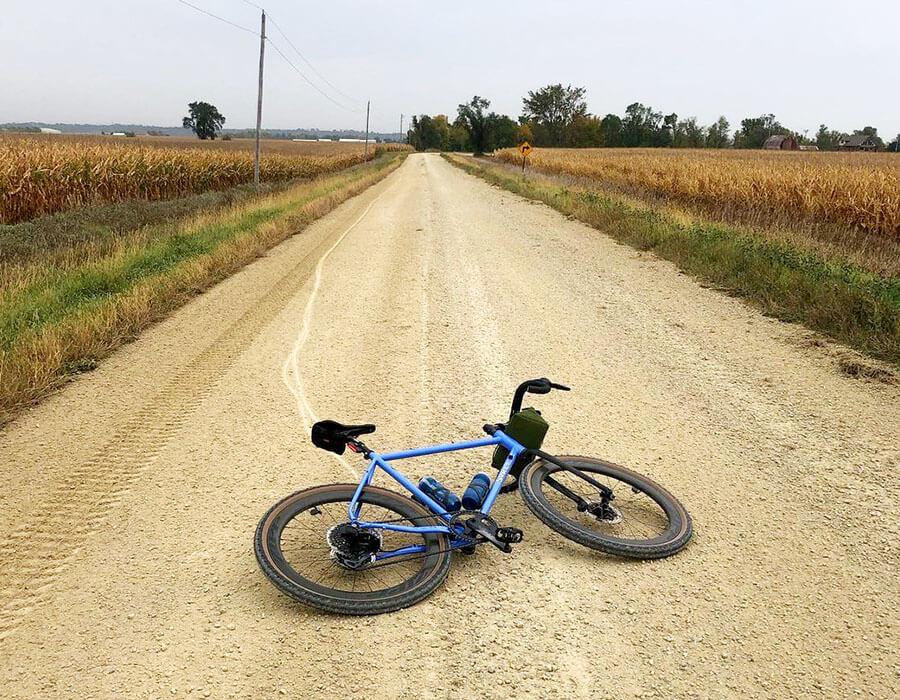 Surly Midnight Special colored in Perry Winkle's Sparkle lying on left side on gravel road between corn fields