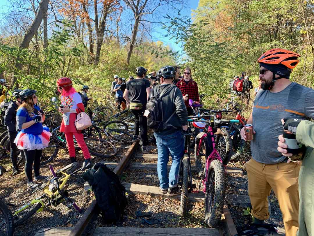 Group of cyclists stand near railroad tracks with their bikes on a sunny day in surrounded by trees with green leaves