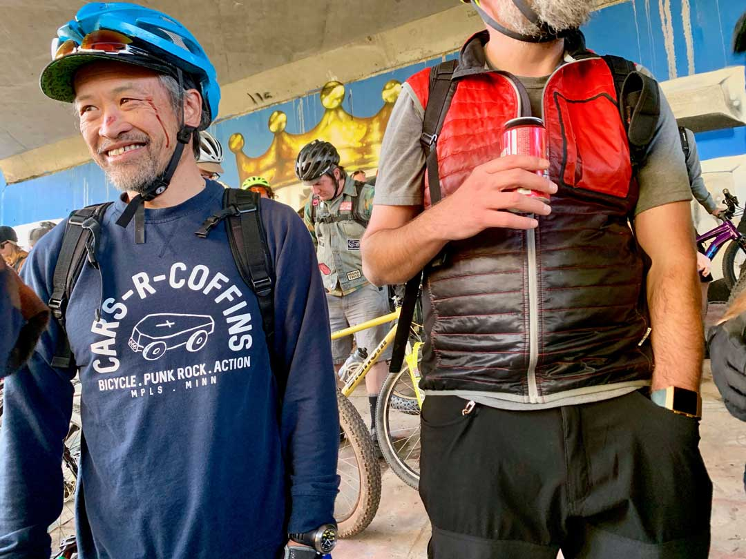 Smiling person with blood near their left eye wearing a blue bike helmet stands next to a person holding a red beer can
