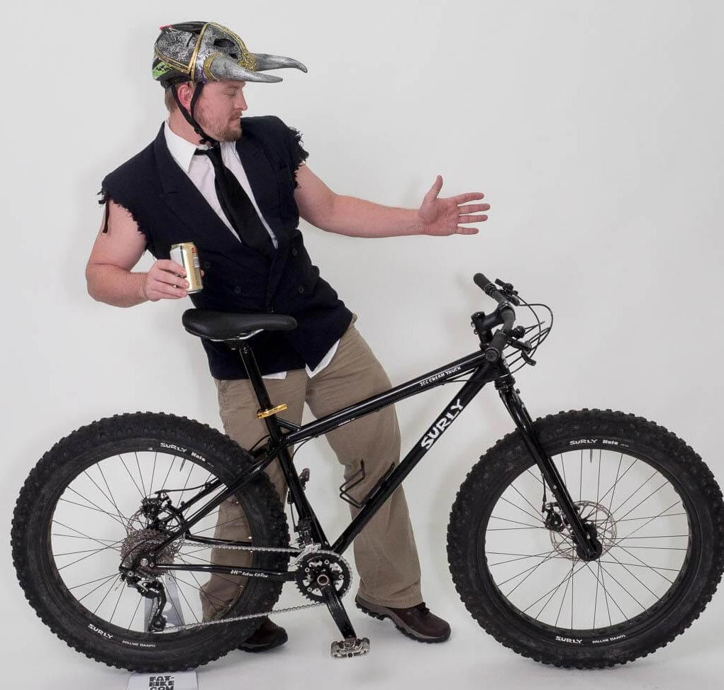 Left view of Surly fat bike with cyclist standing on left side wearing sleeveless suit jacket and tie and horned helmet