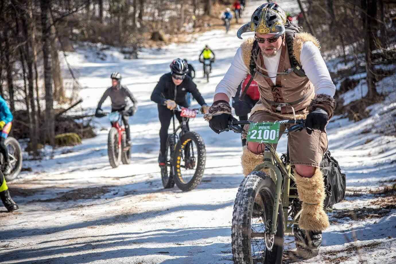 Cyclists ride up an icy road on fat bikes  in the woods with front cyclist wearing viking clothing