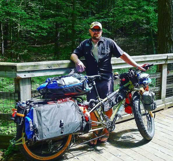 Rider stands on left side of a Surly Big Fat Dummy fat bike loaded with gear, on a wooden trail bridge in the woods