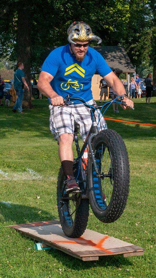 Cyclist riding a Surly Moonlander bike pops up the front end over a small course obstacle