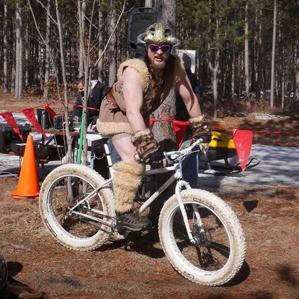 Cyclist wearing viking clothing including bike helmet with horns rides an all white Surly Pugsly bike on a grass trail