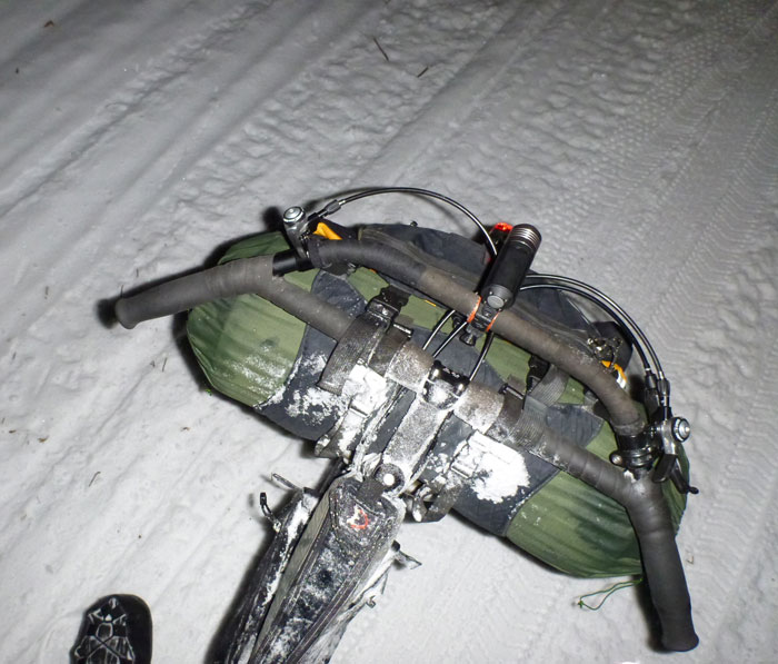 Downward view of a handlebar with a headlight and gear pack, on a bike that's standing on snow at night