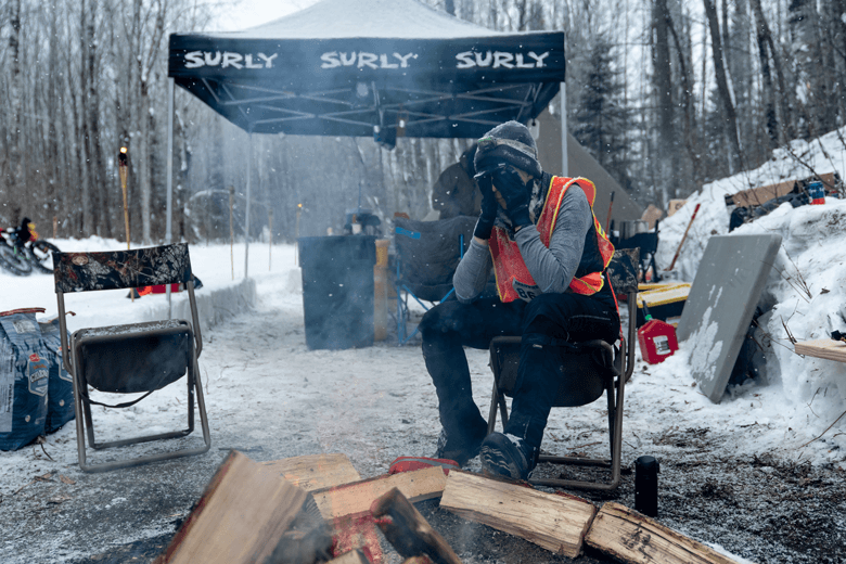 Person wearing mittens and winter gear cover their face while sitting at a chair at a snowy site in the woods