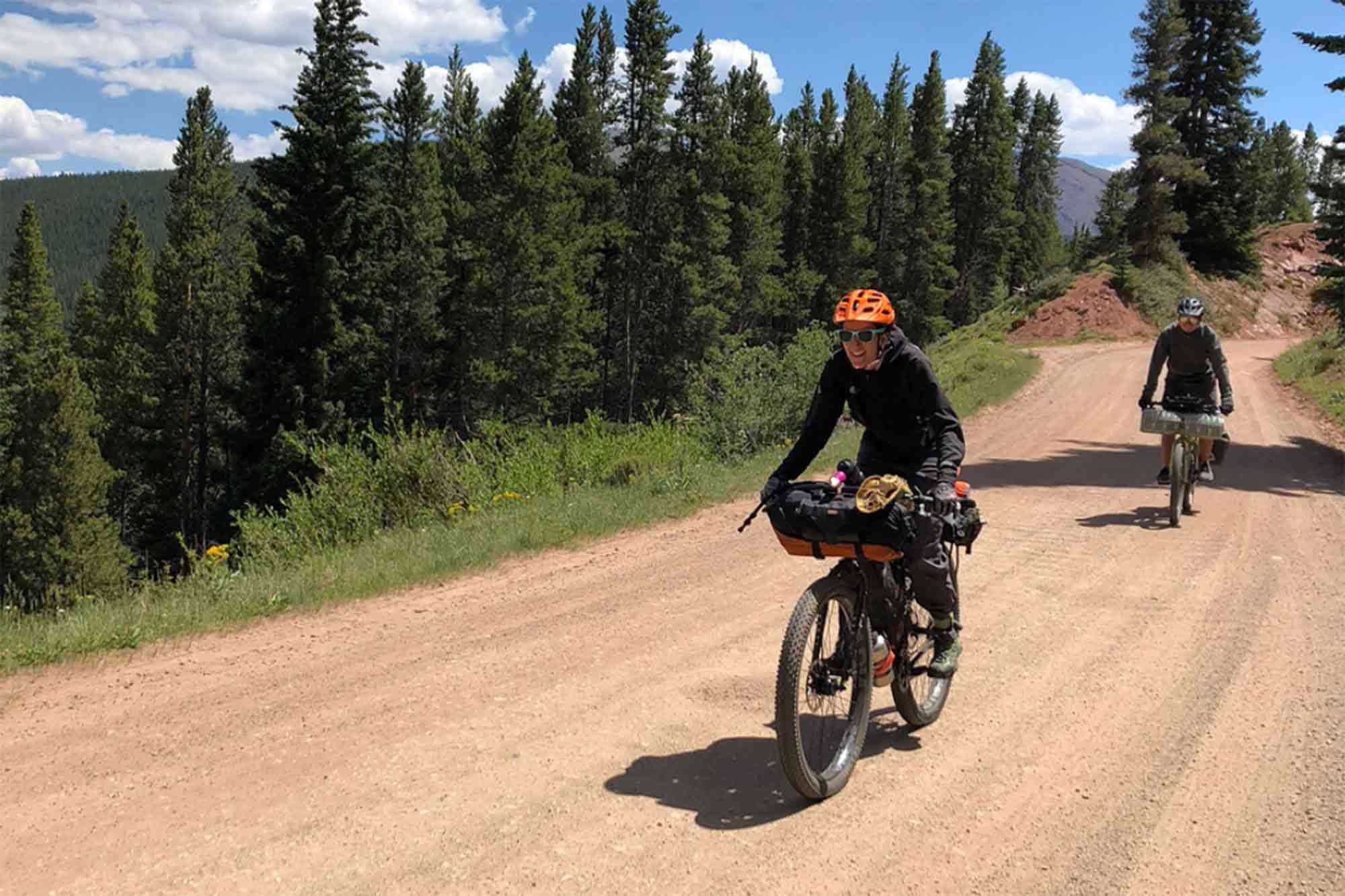 Cyclist smiles riding up a hill on a gravel road in the pine trees to the side with another rider tailing behind