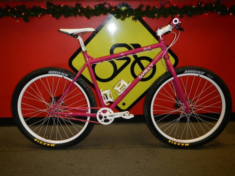 Right side view of a pink Surly 1x1 bike, parked in front of a red wall, with a yellow biking sign painted on it