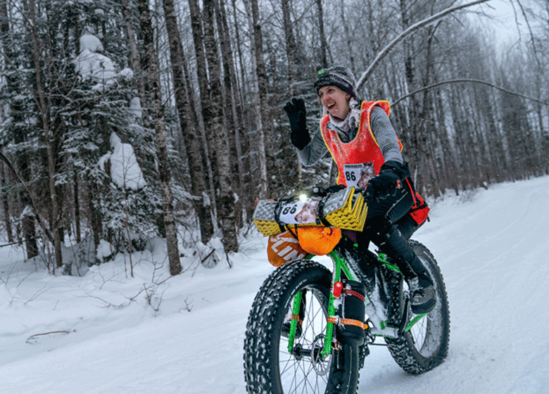 Angled left side view of a winter cyclist  raising their right hand riding down a snow covered hill trail in the woods