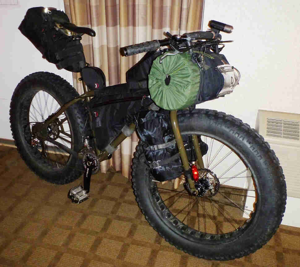 Right side view of an olive drab Surly Moonlander fat bike, loaded with gear, leaning against a wall in a hotel room