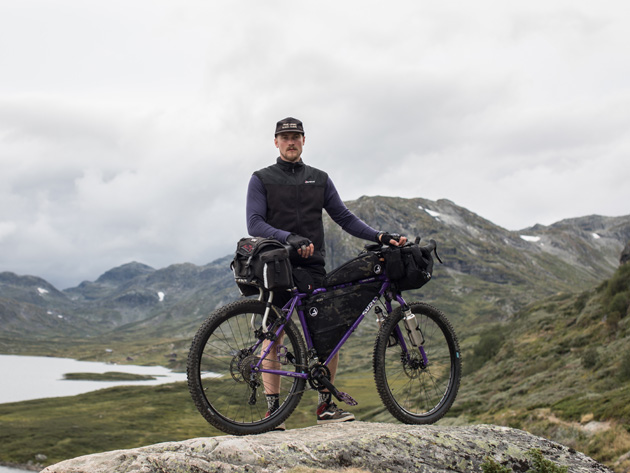 Cyclist standing on a large flat rock on a cloudy day with a lake and mountains in the background