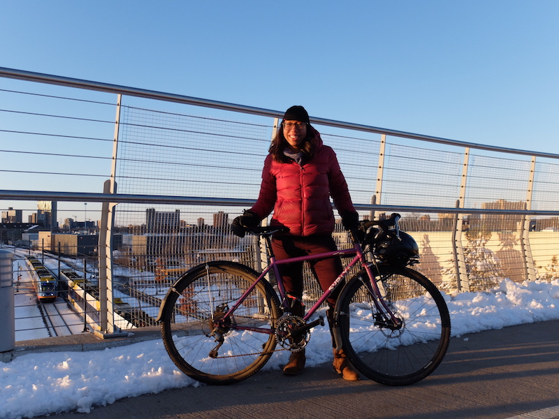 Right side view of a purple Surly Straggler bike, with cyclist standing behind, on a bike bridge with snow on the sides